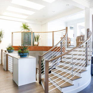 Large coastal wooden curved staircase photo in Orange County with painted risers