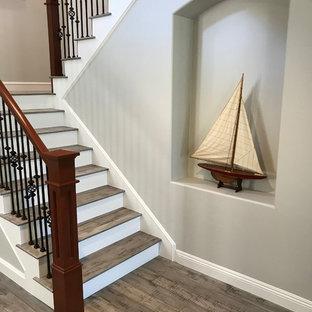 Ejemplo de escalera en L, de estilo americano, grande, con escalones de madera, contrahuellas de madera pintada y barandilla de varios materiales