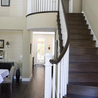 Imagen de escalera curva, clásica, grande, con escalones de madera y contrahuellas de madera