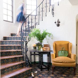 Пример оригинального дизайна: изогнутая лестница в средиземноморском стиле с подступенками из плитки, ступенями из терракотовой плитки и металлическими перилами