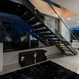 Mid-sized wooden straight glass railing staircase photo in Auckland with glass risers