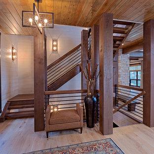 """Esempio di una scala a """"U"""" stile rurale con pedata in legno, nessuna alzata e parapetto in materiali misti"""