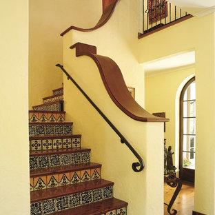 Imagen de escalera en L, mediterránea, con escalones de madera y contrahuellas con baldosas y/o azulejos