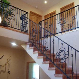 アルバカーキの大きいタイルのサンタフェスタイルのおしゃれなサーキュラー階段 (木の蹴込み板) の写真