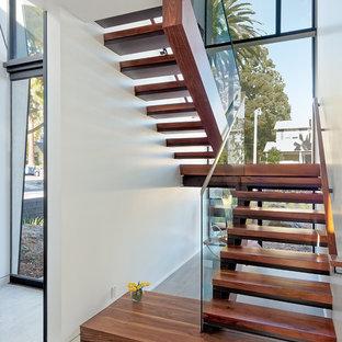 Diseño de escalera suspendida, actual, grande, sin contrahuella, con escalones de madera y barandilla de vidrio