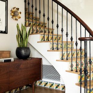 Modelo de escalera curva, mediterránea, con escalones de madera, contrahuellas con baldosas y/o azulejos y barandilla de varios materiales