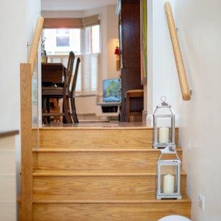 Ispirazione per una scala a rampa dritta minimal di medie dimensioni con pedata in legno, alzata in travertino e parapetto in vetro
