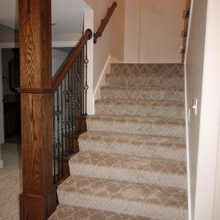 Diseño de escalera en U, clásica, grande, con escalones enmoquetados, contrahuellas enmoquetadas y barandilla de metal