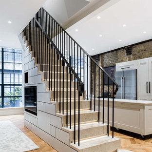ロンドンの広いタイルのインダストリアルスタイルのおしゃれな直階段 (タイルの蹴込み板、金属の手すり) の写真