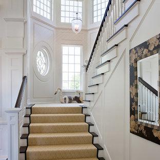 Ejemplo de escalera en U, costera, con escalones de madera y contrahuellas de madera pintada