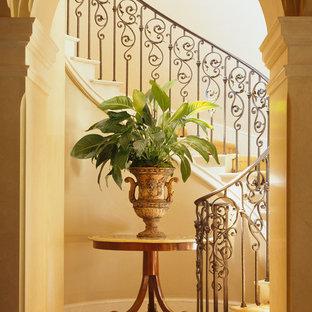Imagen de escalera curva, tradicional, de tamaño medio, con escalones de piedra caliza, contrahuellas de piedra caliza y barandilla de metal