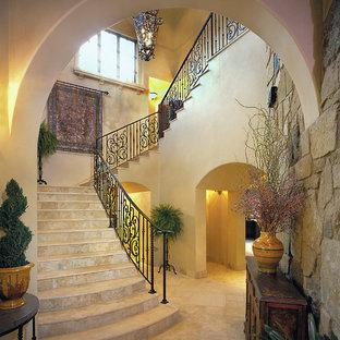 Cette image montre un escalier traditionnel en U avec des marches en travertin, des contremarches en travertin et un garde-corps en métal.