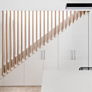 シドニーの中サイズのカーペット敷きのコンテンポラリースタイルのおしゃれな直階段 (カーペット張りの蹴込み板、木材の手すり) の写真