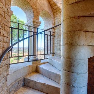Foto de escalera en L, rústica, con escalones de mármol, contrahuellas de mármol y barandilla de varios materiales