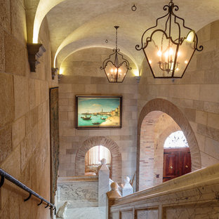 Tuscan marble l-shaped mixed material railing staircase photo in Orange County with marble risers
