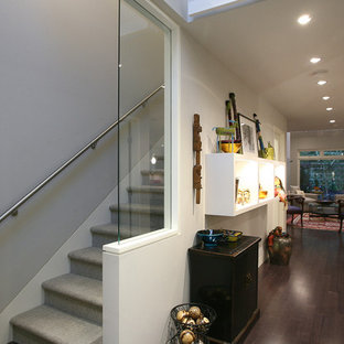 Example of a large trendy carpeted straight glass railing staircase design in Orange County with carpeted risers