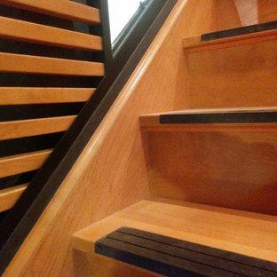 モントリオールの中サイズのコンクリートのエクレクティックスタイルのおしゃれなかね折れ階段 (木の蹴込み板、ガラスの手すり) の写真
