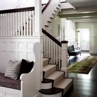 Imagen de escalera en L, clásica, con escalones de madera, contrahuellas de madera pintada y barandilla de madera