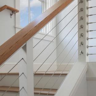 Foto på en funkis trappa i trä, med sättsteg i målat trä och kabelräcke