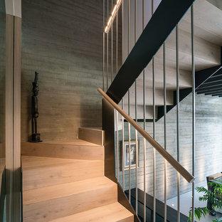 マドリードの中サイズの木のコンテンポラリースタイルのおしゃれな折り返し階段 (木の蹴込み板、木材の手すり) の写真