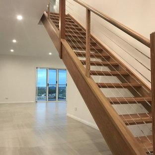 Modelo de escalera recta, minimalista, pequeña, con escalones de madera, contrahuellas de madera y barandilla de cable
