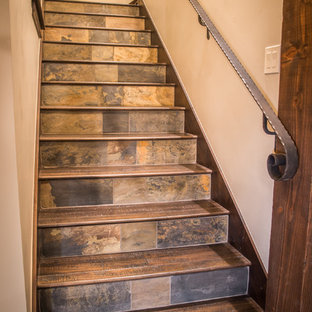 デンバーの木のラスティックスタイルのおしゃれな階段 (スレートの蹴込み板) の写真