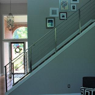デトロイトの中サイズのカーペット敷きのコンテンポラリースタイルのおしゃれな直階段 (カーペット張りの蹴込み板、金属の手すり) の写真