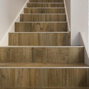 Ejemplo de escalera recta, minimalista, de tamaño medio, con escalones con baldosas y contrahuellas con baldosas y/o azulejos