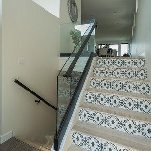 Diseño de escalera en U, minimalista, grande, con escalones de madera, contrahuellas con baldosas y/o azulejos y barandilla de vidrio
