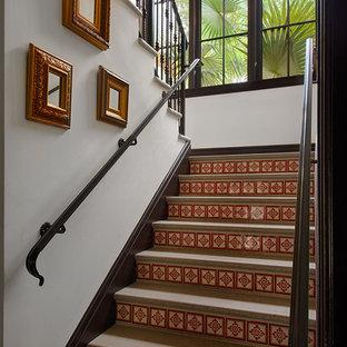 Foto de escalera en U, tropical, de tamaño medio, con contrahuellas con baldosas y/o azulejos