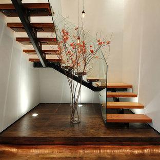 """Ispirazione per una grande scala a """"U"""" industriale con pedata in legno, nessuna alzata e parapetto in vetro"""