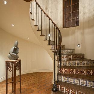 Diseño de escalera curva, mediterránea, con escalones de madera y contrahuellas con baldosas y/o azulejos