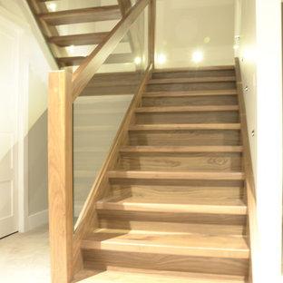 Diseño de escalera en L, moderna, de tamaño medio, sin contrahuella, con escalones de madera y barandilla de vidrio