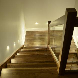 Diseño de escalera en L, minimalista, de tamaño medio, sin contrahuella, con escalones de madera y barandilla de vidrio