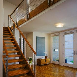 Diseño de escalera actual, sin contrahuella, con escalones de madera y barandilla de cable
