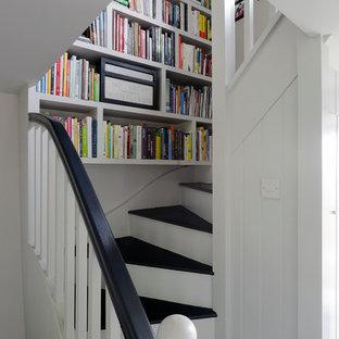 Пример оригинального дизайна интерьера: маленькая изогнутая лестница в стиле кантри с деревянными ступенями и крашенными деревянными подступенками