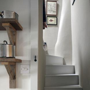Modelo de escalera curva, de estilo de casa de campo, pequeña, con escalones de madera pintada y contrahuellas de madera pintada
