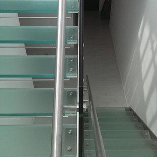 Foto di una scala a rampa dritta minimalista di medie dimensioni con pedata in vetro, nessuna alzata e parapetto in vetro
