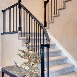 デンバーの中サイズのカーペット敷きのトラディショナルスタイルのおしゃれな折り返し階段 (カーペット張りの蹴込み板、木材の手すり) の写真