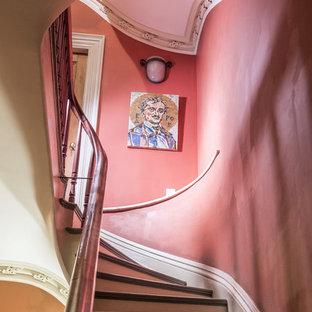 Ejemplo de escalera curva, ecléctica, con escalones de madera y barandilla de madera