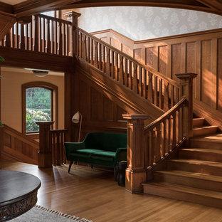 Diseño de escalera en L, de estilo americano, grande, con escalones de madera, contrahuellas de madera y barandilla de madera