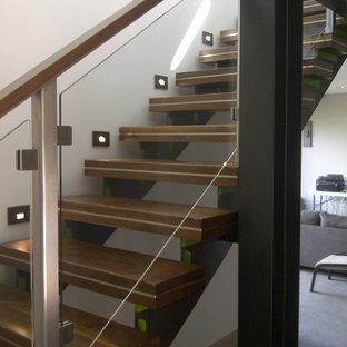 Esempio di una scala sospesa moderna di medie dimensioni con pedata in legno e nessuna alzata