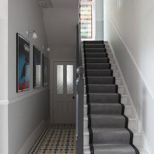 Imagen de escalera recta y boiserie, actual, grande, con escalones de madera pintada, contrahuellas de madera pintada, barandilla de madera y boiserie