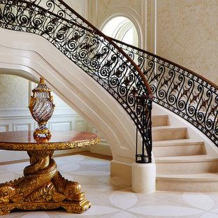 Imagen de escalera curva, mediterránea, extra grande, con escalones de mármol, contrahuellas de mármol y barandilla de varios materiales