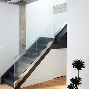 Imagen de escalera en L, urbana, con escalones de madera pintada, contrahuellas de madera pintada y barandilla de vidrio