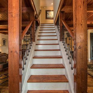 ワシントンD.C.の中くらいの木のラスティックスタイルのおしゃれな直階段 (フローリングの蹴込み板、金属の手すり) の写真