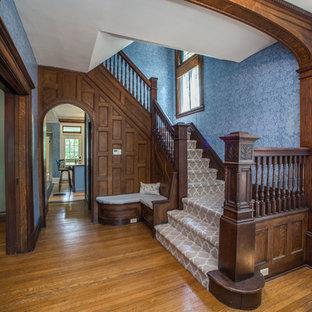 他の地域のカーペット敷きのヴィクトリアン調のおしゃれな折り返し階段 (カーペット張りの蹴込み板、木材の手すり) の写真