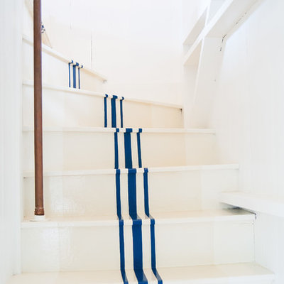 Mid-sized beach style painted curved staircase photo in Other with painted risers