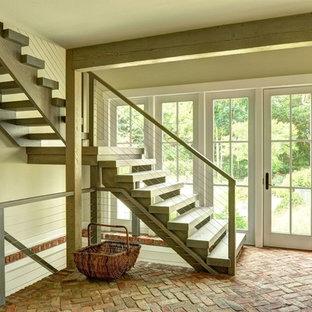 Пример оригинального дизайна: большая угловая лестница в стиле кантри с деревянными ступенями без подступенок