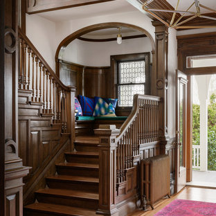 Example of a transitional wooden u-shaped wood railing staircase design in Portland with wooden risers